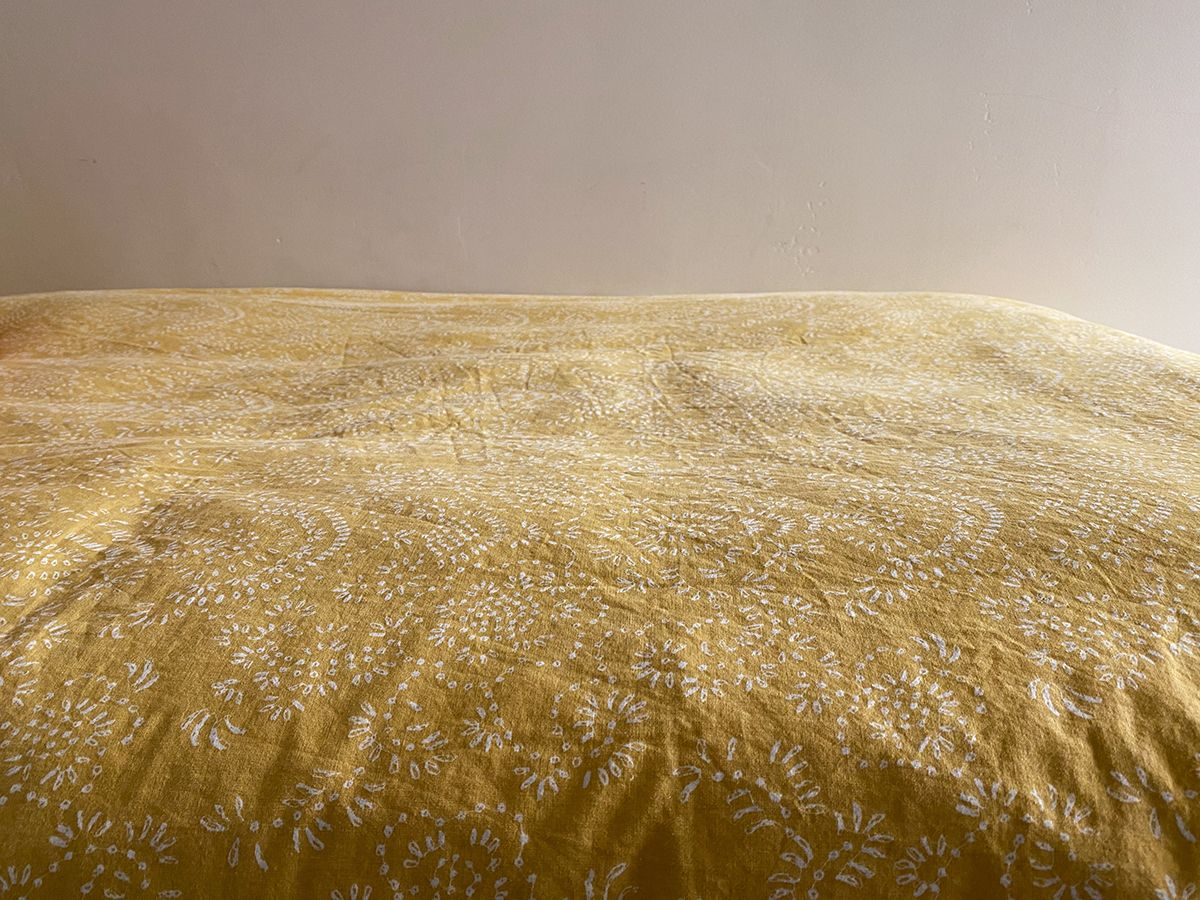 A lightly-wrinkled gold-ish/yellow-ish bedspread with a faint white floral pattern, in front of a blank wall.